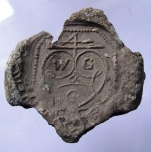 große Tuchplombe: oben das Segenszeichen 4, darunter Herz u. Initialen (Material: Blei)