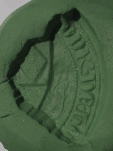 Bruchstück eines Siegelstempels mit Resten der gotischen Majuskeln und dem Wappen, Mittelalter, Abdruck