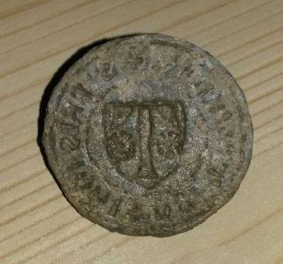 mittelalterliches Petschaft aus Blei, Umschrift in gothischen Majuskeln, im Wappen ein T, links und rechts davon jeweils 1 Blüte, etwa 14.Jh.
