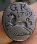 """Siegelring, vermutlich aus Arsenbronze, datierte Siegelfläche 1769 mit springendem Pferd nach links, darüber die Initialen """"GK"""", gespiegelt"""